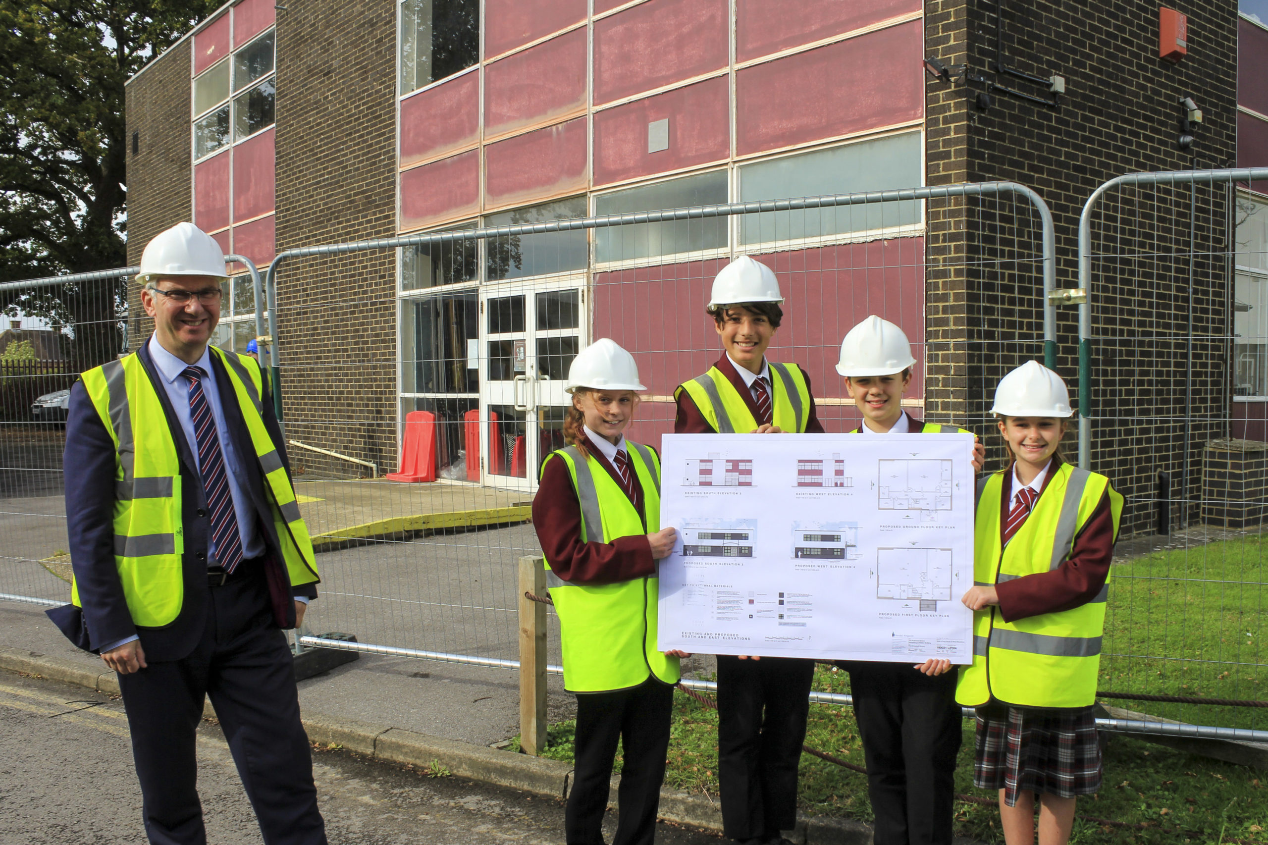 Nigel Pressnell, headteacher of The Arnewood School, with pupils holding the new plans